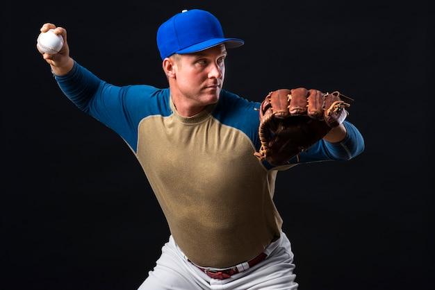 Homme Posant Avec Un Gant De Baseball Et Une Balle Photo gratuit