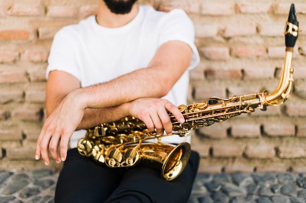 Homme posant avec saxophone dans la rue Photo gratuit