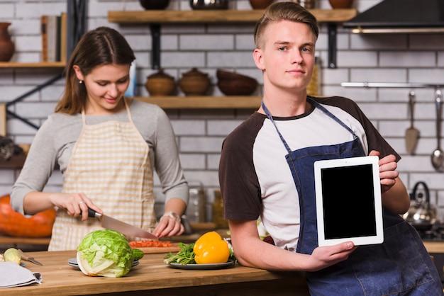Homme posant avec tablette en cuisinant Photo gratuit