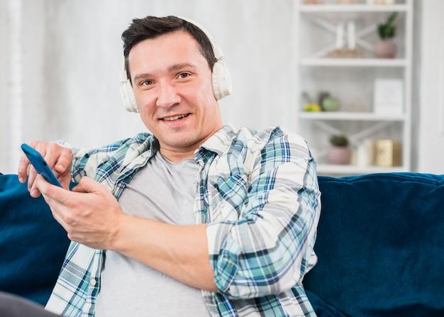Homme positif écoute de la musique au casque et navigation sur smartphone sur un canapé Photo gratuit