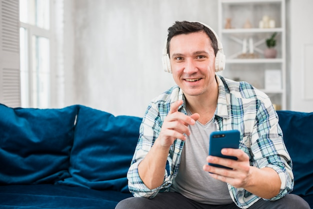 Homme positif écoute de la musique au casque et tenant un smartphone sur un canapé Photo gratuit