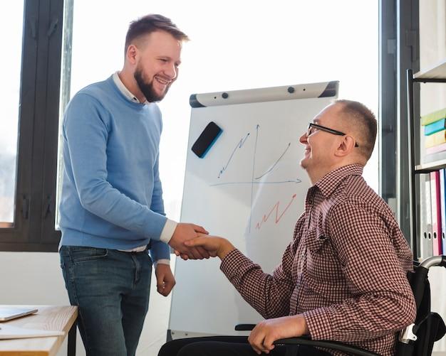 Homme Positif Félicitant L'homme Handicapé Pour Son Engagement Photo gratuit