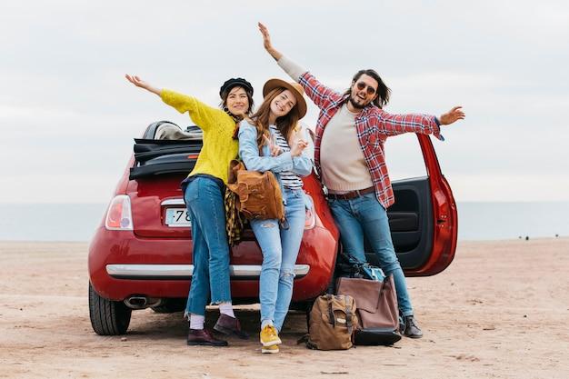 Homme positif avec les mains en l'air près de femmes embrassant et voiture sur la plage de la mer Photo gratuit