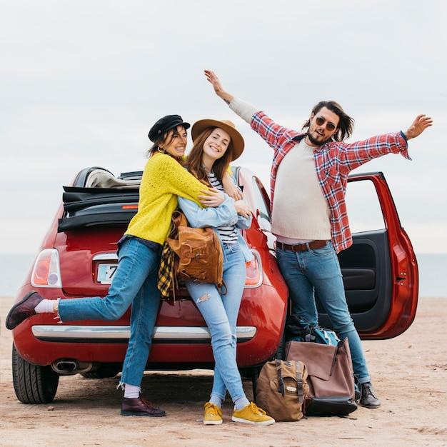 Homme positif avec les mains en l'air près de femmes embrassant et voiture sur la plage Photo gratuit