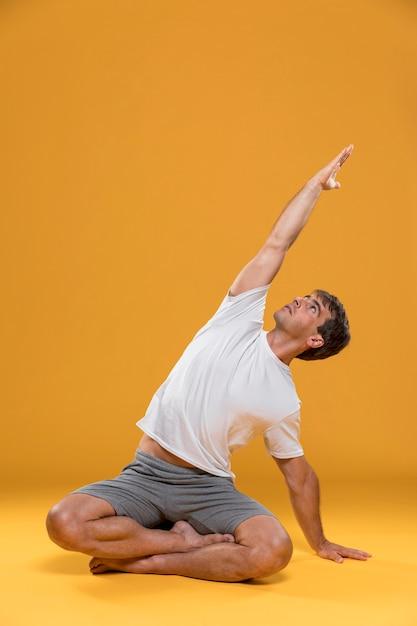 Homme pratiquant la pose de yoga Photo gratuit
