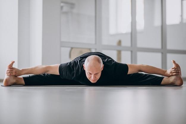 Homme pratiquant le yoga dans la salle de sport Photo gratuit