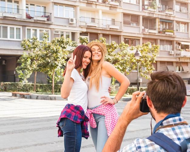 Homme prenant une photo de deux femmes heureuses devant la caméra Photo gratuit