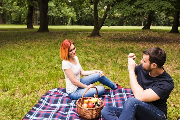 Homme prenant une photo de sa petite amie sur un téléphone portable au pique-nique Photo gratuit