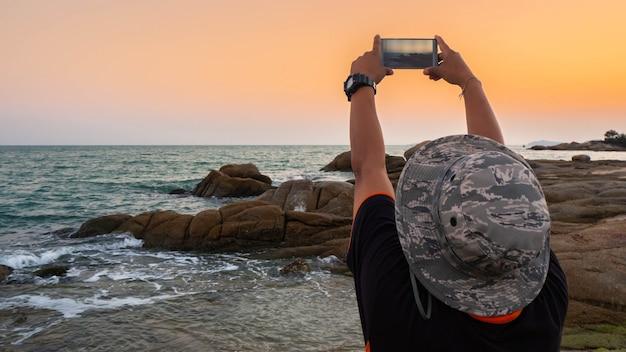 Homme prenant des photos du coucher de soleil avec téléphone portable Photo Premium