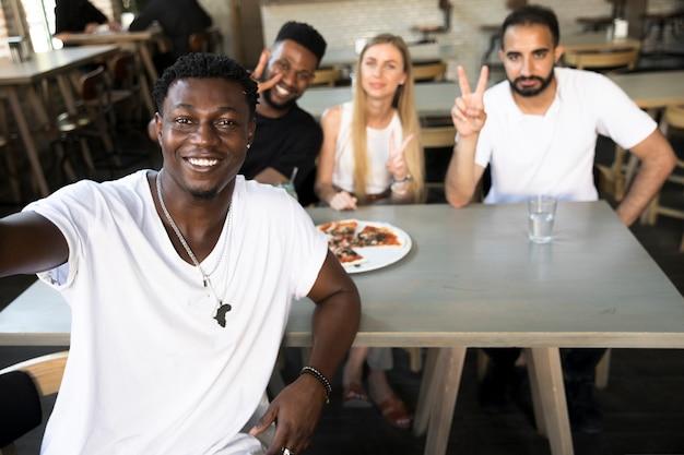 Homme prenant un selfie avec des amis interraciaux Photo gratuit