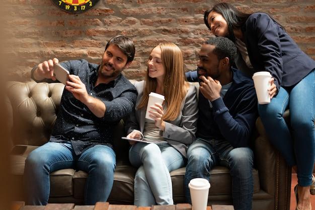 Homme prenant selfie sur un canapé avec des collègues Photo Premium
