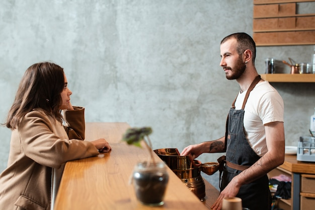 Homme préparant un café et parlant à une femme Photo gratuit