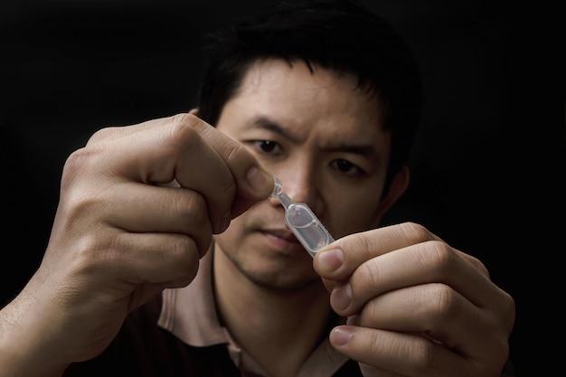 Homme préparant la médecine des gouttes pour les yeux guérir sa douleur aux yeux avec fond noir Photo gratuit
