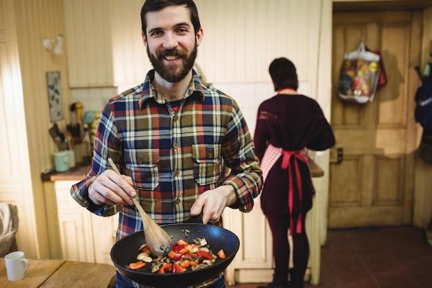 Homme préparant des plats en cuisine Photo gratuit