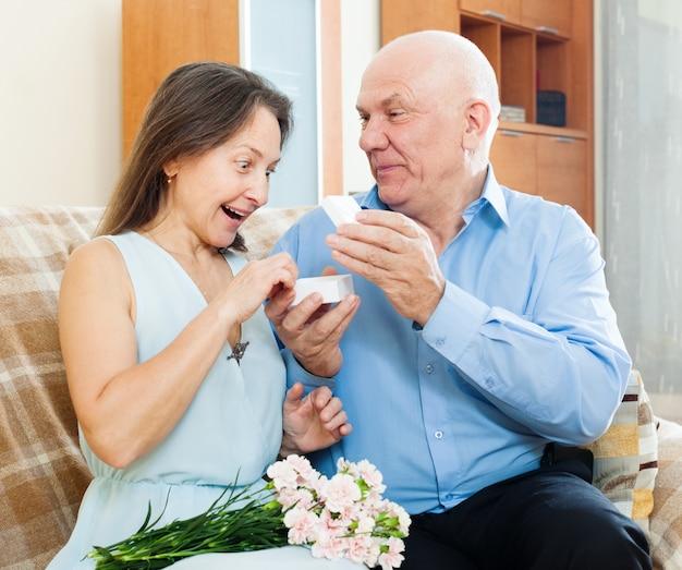 Homme présentant un bijou de femme surprise Photo gratuit