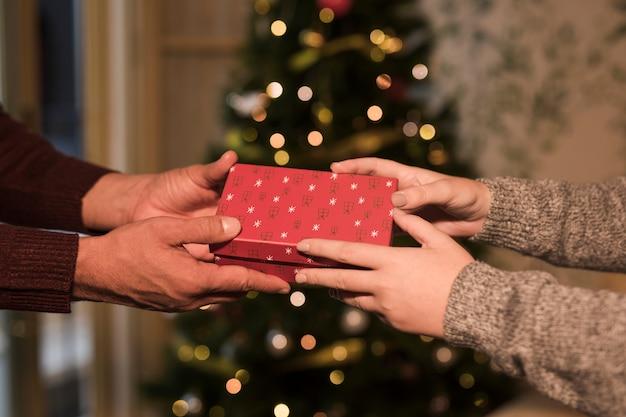 Homme présentant une boîte-cadeau à une femme près d'un arbre de noël Photo gratuit