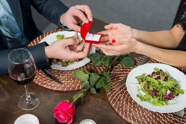 Homme présentant une boîte-cadeau pour femme à table avec assiettes, rose et verre Photo gratuit