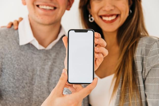 Homme présentant un nouveau téléphone Photo gratuit