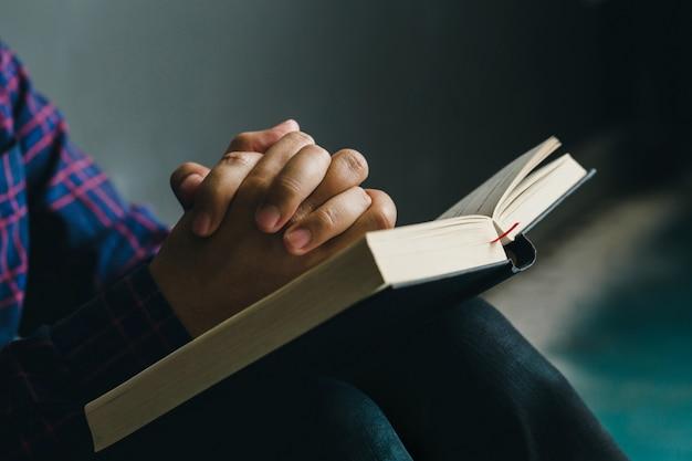 Homme Priant Sur La Sainte Bible Le Matin. Main De Garçon Avec La Bible En Prière, Chrétiens Et Concept D'étude De La Bible. Photo Premium