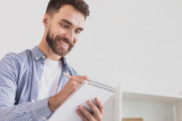 Homme productif écrivant dans le bloc-notes Photo gratuit