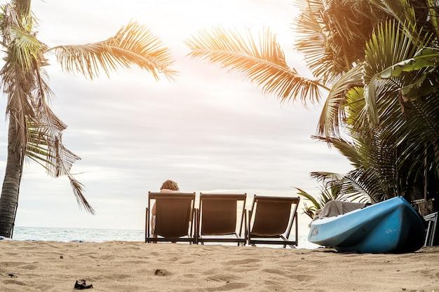 Un Homme Profitant De La Vue Imprenable Sur La Plage De Sable Tropicale Avec Ses Palmiers Verts Et Son Bel Océan Photo Premium