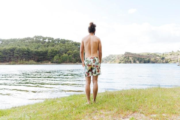 Homme profitant d'une vue sur le lac Photo gratuit