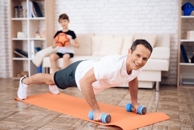 L'homme push-up, tenant un haltère. Photo Premium