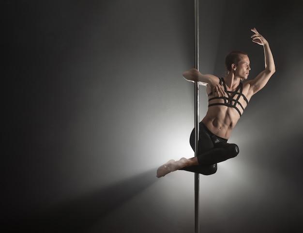 Homme avec pylône danseur de pôle mâle dansant sur un fond noir Photo Premium