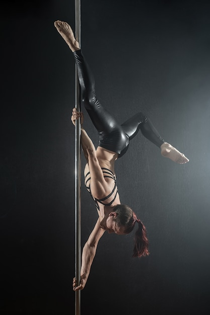 Homme avec pylône. danseur de pôle mâle danser sur un fond noir Photo Premium