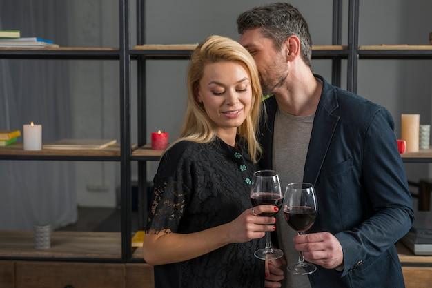 Homme qui chuchote dans une femme blonde avec des verres de vin Photo gratuit
