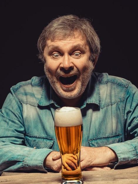 L'homme Qui Crie En Chemise En Jean Avec Un Verre De Bière Photo gratuit