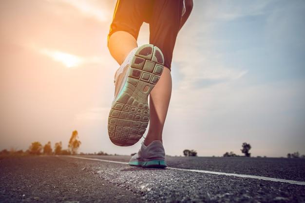 Homme qui fait du jogging sur une route avec le soleil. Photo Premium