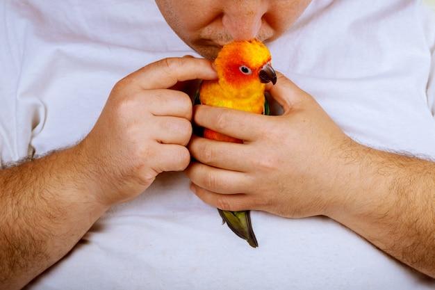 Homme qui joue avec son perroquet tenant coloré Photo Premium
