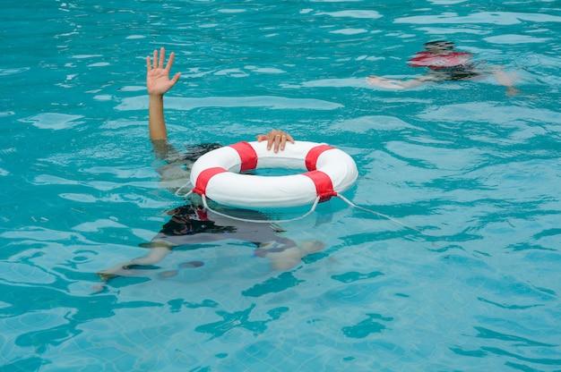 Un homme qui se noie lève les mains au secours dans la piscine, Photo Premium