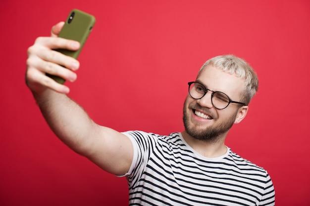 Homme De Race Blanche Blonde Avec Des Lunettes Faisant Un Selfie Sur Un Mur Rouge Photo Premium
