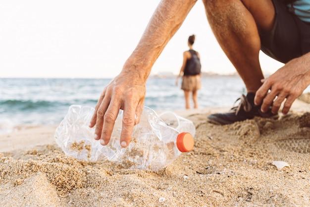 Homme ramassant du plastique à la plage Photo Premium