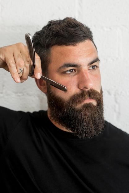 Homme avec rasoir en studio Photo gratuit