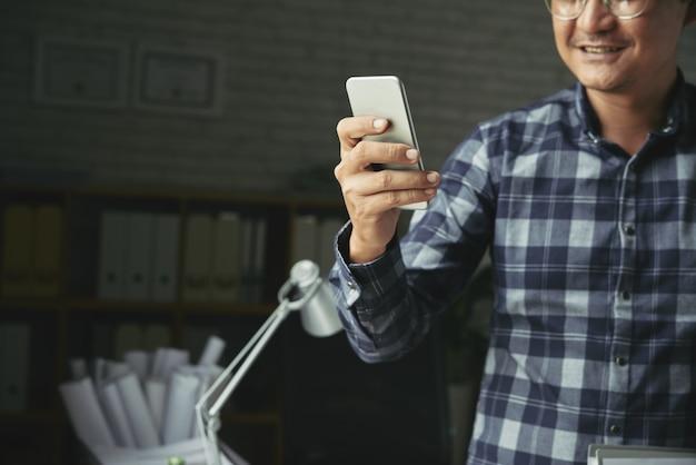 Homme recadré avec application mobile en souriant Photo gratuit