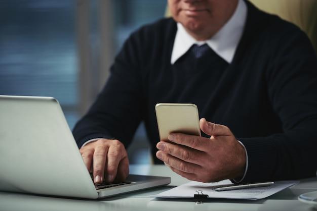 Homme Recadré Vérifiant Les Messages Sur Son Téléphone Au Bureau Photo gratuit