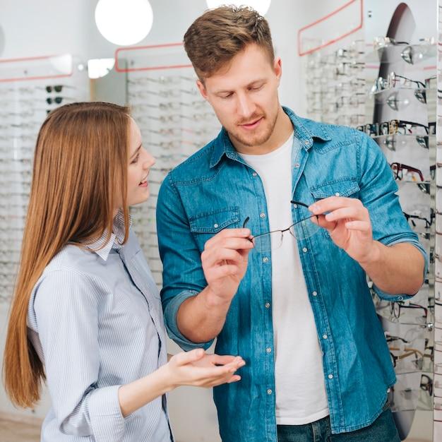 Homme à la recherche de nouvelles lunettes chez l'optométriste Photo gratuit