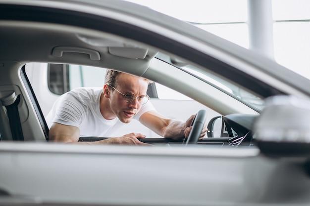 Homme à la recherche d'une voiture dans une salle d'exposition Photo gratuit