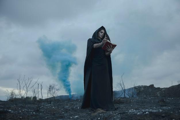 Homme récitant des citations d'un livre avec des effets de fumée bleue Photo gratuit