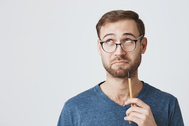 Homme Réfléchi à Lunettes à La Recherche D'inspiration, Tenir Un Crayon Et Détourner Le Regard Photo gratuit