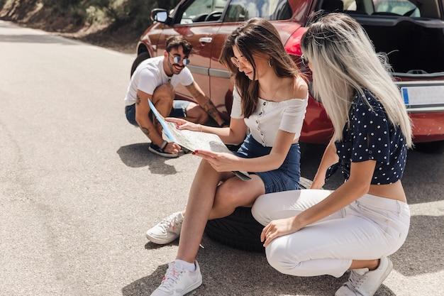 Homme regardant les amies en regardant la carte près de la voiture en panne sur la route Photo gratuit