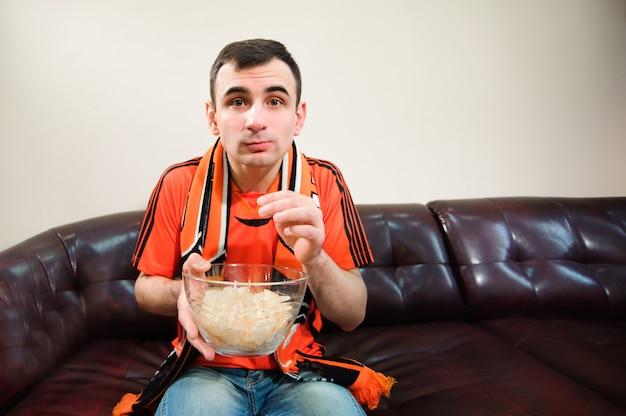 Homme regardant le football, fan de football, sportif à la maison. Photo Premium