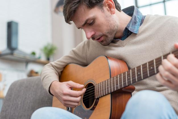 Homme Regardant La Guitare Et Joue Photo gratuit