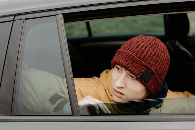 Homme regardant par la fenêtre de la voiture Photo gratuit