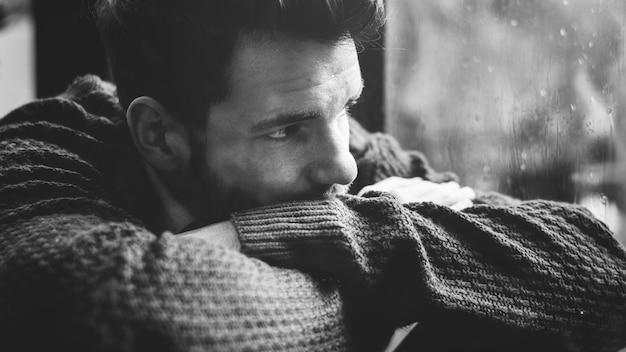 Homme Regardant Par La Fenêtre Photo gratuit