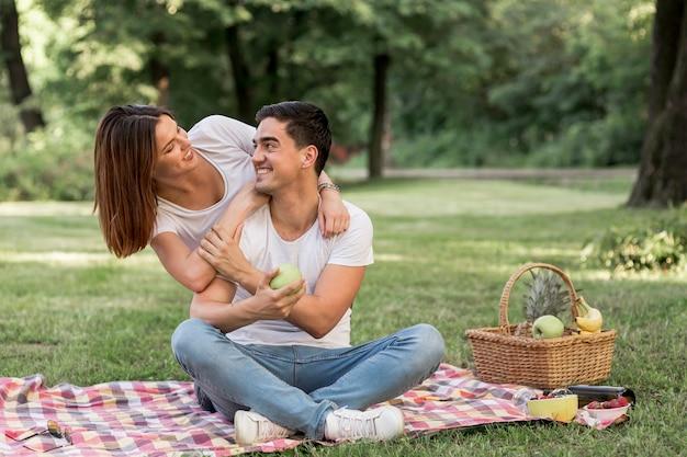 Homme regardant sa petite amie en tenant une pomme Photo gratuit