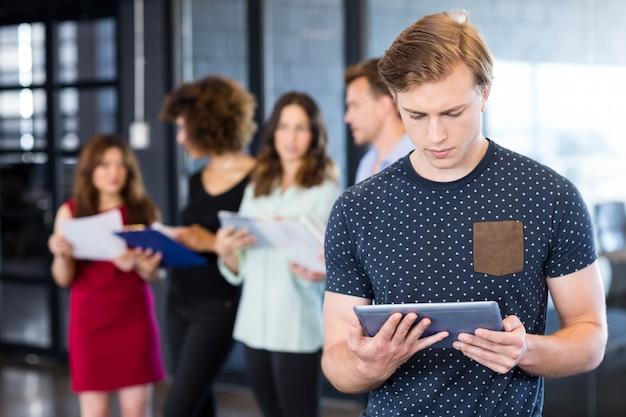 Homme regardant une tablette numérique pendant que ses collègues se tiennent derrière au bureau Photo Premium